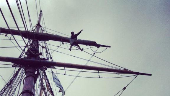 Hewitt climbs across a tall ship