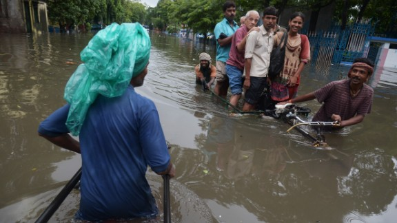 Indian rickshaw pullers carry passengers through a flooded street in Kolkata on October 26.