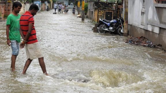 Pedestrians wade on a flooded street following heavy rain in Saroornagar on October 25.