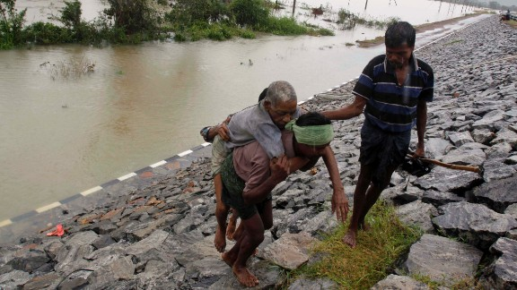 A villager carries an elderly man to safety after crossing floodwaters in Khurda district in the eastern Indian state of Orissa on Friday, October 25.