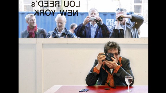 Reed takes a picture during the opening of his exhibition Lou Reed