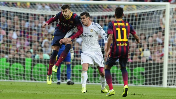Real Madrid's Welsh striker Gareth Bale (C) vies with Barcelona's defender Gerard Pique during the Spanish league Clasico football match FC Barcelona vs Real Madrid CF at the Camp Nou stadium in Barcelona on October 26, 2013. AFP PHOTO / JOSEP LAGOJOSEP LAGO/AFP/Getty Images