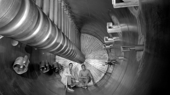 Two scientists show the scale of an earlier accelerator at the U.S. Department of Energy