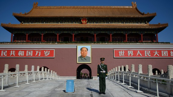 A paramilitary policeman stands before a portrait of Mao Zedong (back C) at Tiananmen Gate and the Forbidden City in Beijing on October 29, 2013.