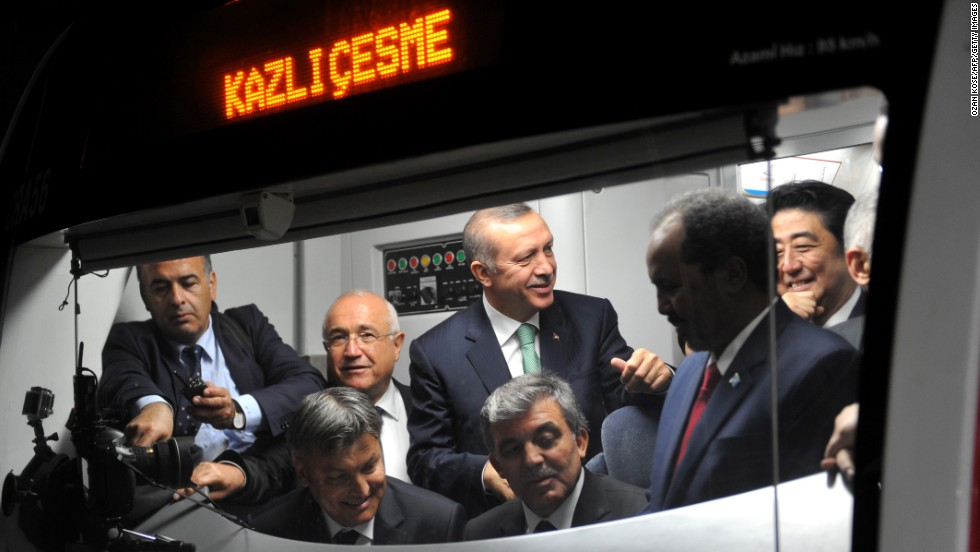 Turkish President Abdullah Gul, seated right, listens to a driver's explanations in the cabin of a Marmaray train Tuesday. Also in the cabin are Turkish Prime Minister Recep Tayyip Erdogan, behind Gul in the green tie; Somali President Hasan Sheikh Mahmud, second from right; and Japanese Prime Minister Shinzo Abe, far right.