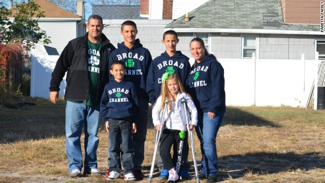 The Panetta family stands in the empty lot where their home once stood.
