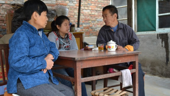 Li Xue sits with her parents at their Beijing home.