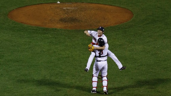 Boston Red Sox relief pitcher Koji Uehara jumps into David Ross' arms after defeating the St. Louis Cardinals.