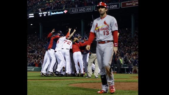 The Red Sox celebrate as St. Louis Cardinals second baseman Matt Carpenter leaves the field.