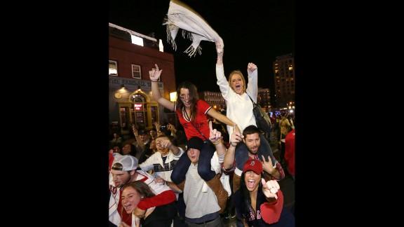 Fans celebrate on the street near Fenway Park.