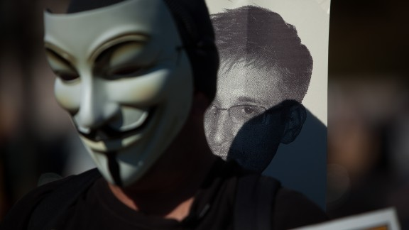 WASHINGTON, DC - OCTOBER 26, 2013: A protester wearing the mask often seen during the Occupy protests, marches with a sign featuring the likeness of former National Security Agency employee Edward Snowden during the Stop Watching Us Rally protesting surveillance by the U.S. National Security Agency, on October 26, 2013, in front of the U.S. Capitol building in Washington, D.C. The rally began at Union Station and included a march that ended in front of the U.S. Capitol building and speakers such as author Naomi Wolf and former senior National Security Agency senior executive Thomas Drake. (Photo by Allison Shelley/Getty Images)
