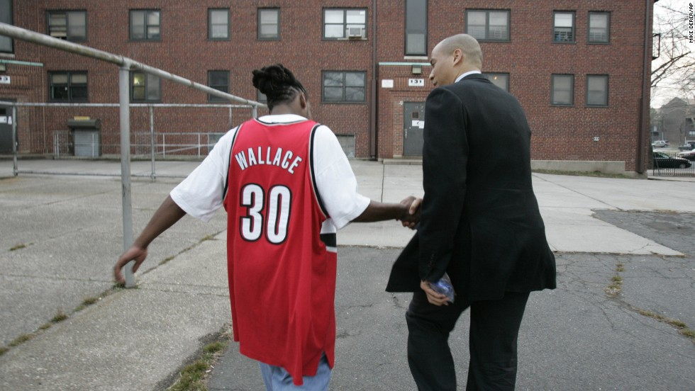 Booker greets a Newark resident at a public housing complex while campaigning for mayoral votes in March 2006.
