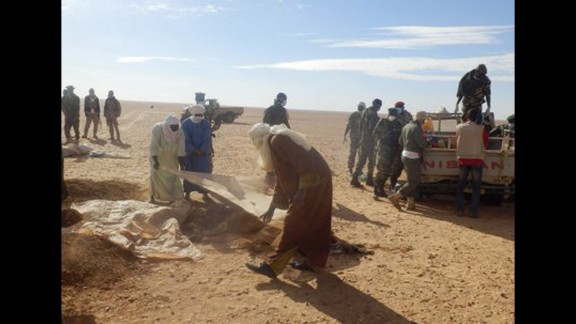 Men cover the bodies of the migrants. Ninety-two bodies have been found, Niger security forces said Thursday. Most of the victims were women and children.