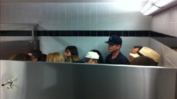 People hide inside a bathroom stall at the airport after the gunshots were reported.