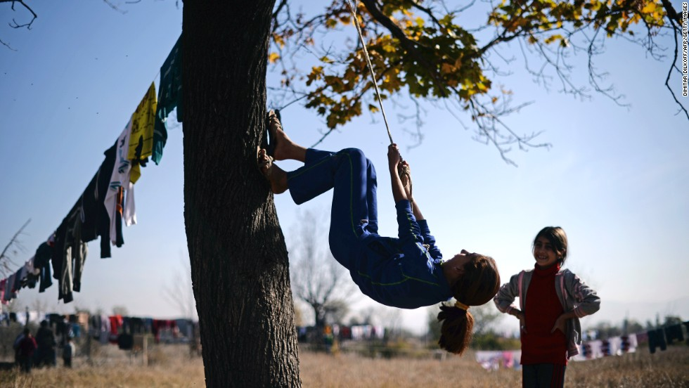 A Syrian refugee uses a rope to climb a tree at the Vrazhdebna shelter on Tuesday, October 29.