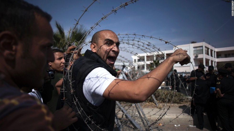 A Morsy supporter shouts at a police officer in Cairo. More than 100 pro-Morsy demonstrators faced a cordon of security forces behind barbed wire.