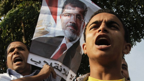 """Morsy supporters raise a poster that reads """"no to the coup"""" in Arabic."""