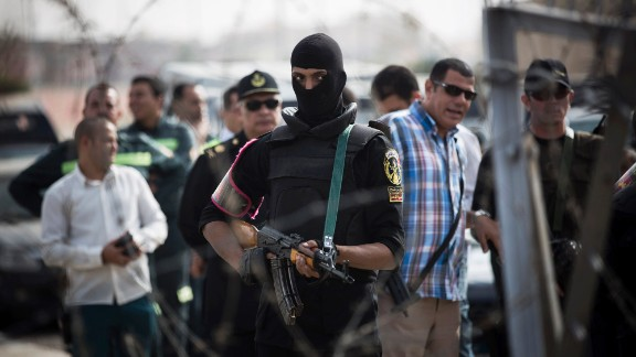 A masked police officer stands guard outside of the police academy compound where Morsy's trial was held.