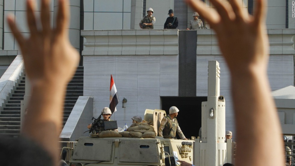 A Morsy supporter raises his hands in front of army soldiers guarding the Supreme Constitutional Court.