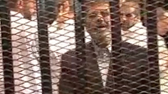 """This image, made from video provided by Egypt's Interior Ministry, shows Morsy speaking from the defendant's cage as he stands with co-defendants during his hearing. """"I am Dr. Mohamed Morsy, the President of the republic,"""" Morsy said. """"The coup is a crime and ... treason."""""""