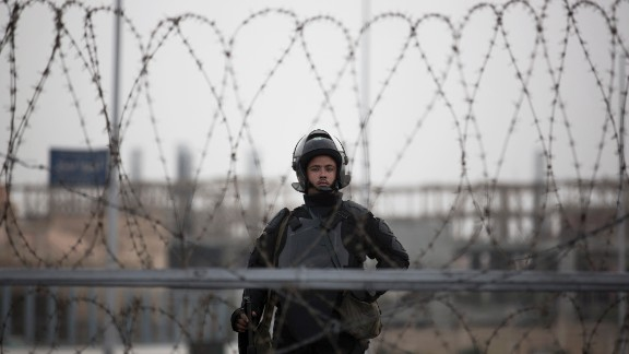 A police officer stands guard behind barbed wire.