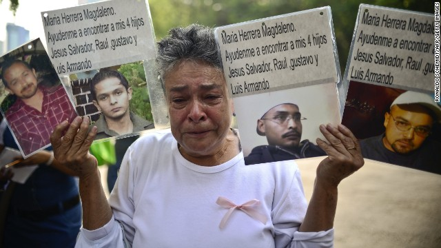 A woman shows pictures of relatives missing in  Mexico's drug war at a rally of mothers whose children have disappeared.