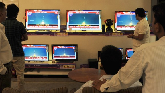 Indian bystanders watch a bank of screens showing the live telecast of the launch of India