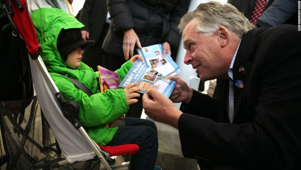 Cuccinelli's Democratic opponent, Terry McAuliffe, passes a campaign flyer to a child as he greets commuters at a Metro station in Fairfax, Virginia.