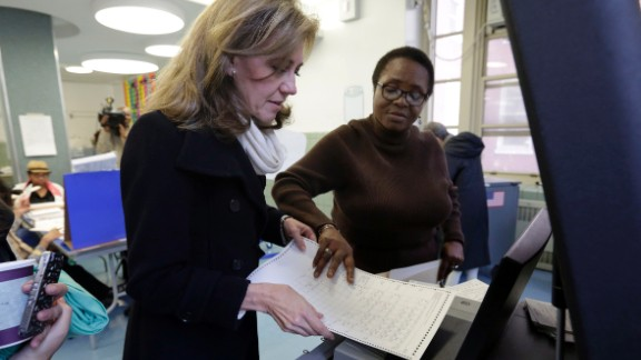 Silda Wall Spitzer, wife of former New York Gov. Eliot Spitzer, has her ballot scanned by Edith Maduakolam at Public School 6.