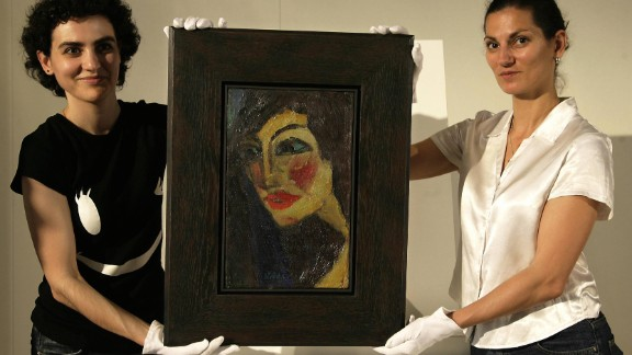 """Auction assistants hold German expressionist painter Emil Nolde's portrait """"Nadja,"""" in Munich in 2007. The picture, which was considered missing for decades, was found in an attic in Germany. Works by Nolde were among those rediscovered in Munich in 2012."""