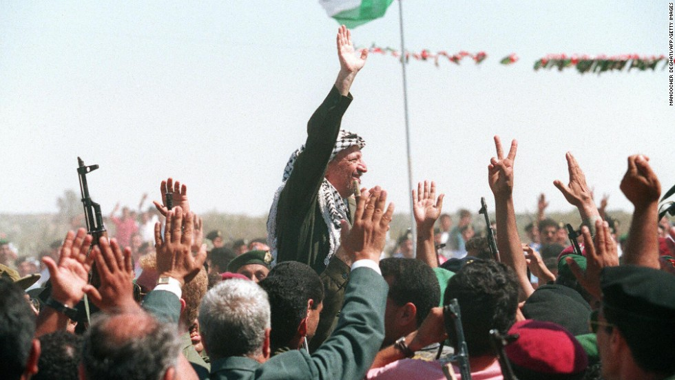 On July 1, 1994, Arafat waves to a crowd of cheering Palestinians as he crosses the border into Gaza for the first time in 27 years.