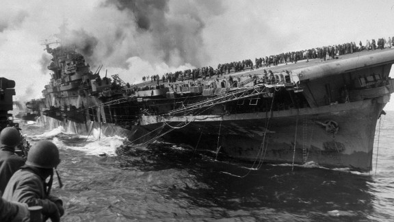 "The Essex-class USS Franklin burns after being hit by a Japanese dive bomber in 1945. The ship was named after Benjamin Franklin and nicknamed ""Big Ben."""