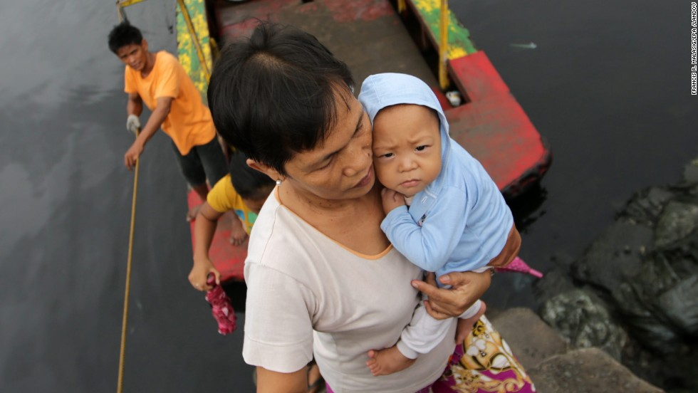 A woman carries a baby across a river November 8 at a coastal village in Las Pinas, Philippines.