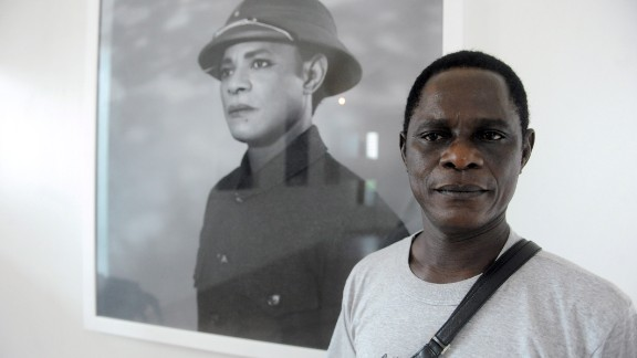 """Samuel Fosso poses next to his self portrait, in which he transforms into Chinese leader Mao Zedong for his latest photographic series titled """"The Emperor of Africa,"""" premiered at this year's LagosPhoto Festival."""