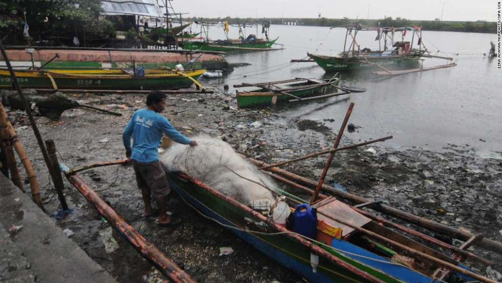 A resident unloads nets off a fishing boat in Bacoor on November 8.