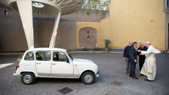 Francis has eschewed fancy cars. Here, Father Don Renzo Zocca, second from right, offers his white Renault 4L to the Pope during a meeting at the Vatican in September 2013.