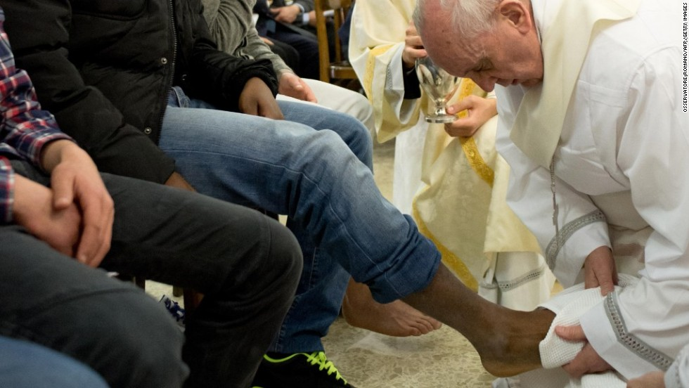 The Pope washes the feet of juvenile offenders, including Muslim women, as part of Holy Thursday rituals in March 2013. The act commemorates Jesus' washing of the Apostles' feet during the Last Supper.