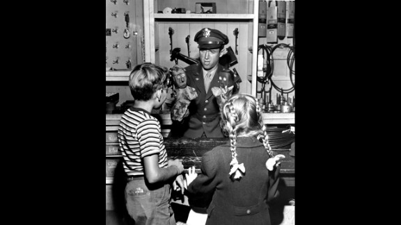 Stewart entertains some local children at his father's hardware store with puppets he made when he was 7 years old.