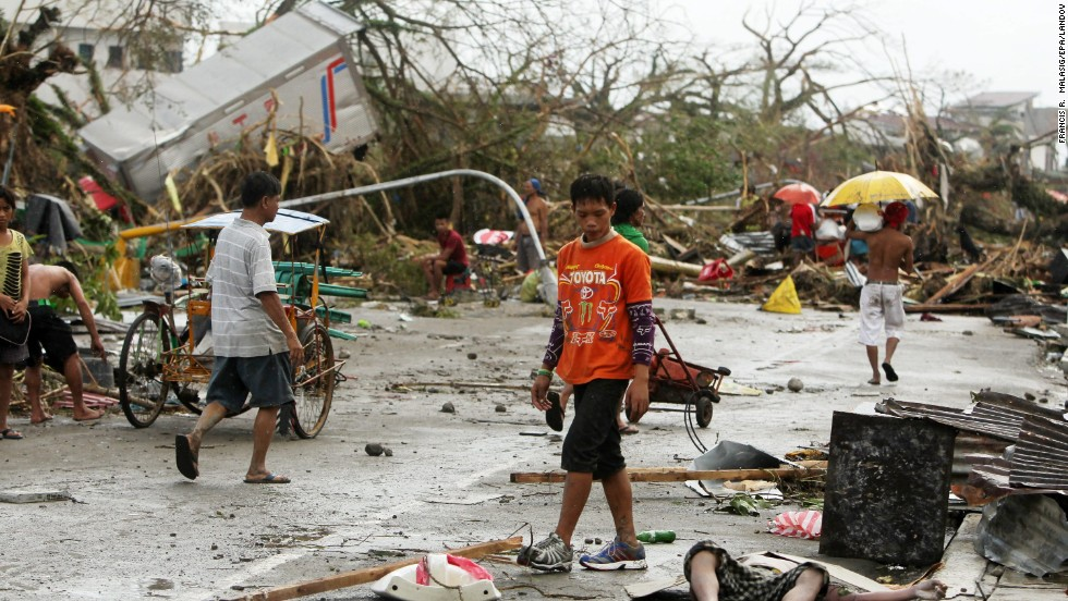 People walk past a victim left on the side of a road in Tacloban.