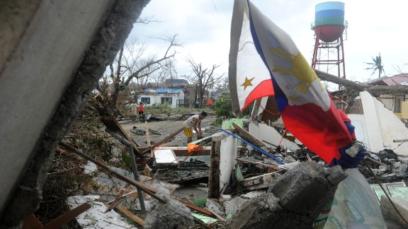 A man searches for salvageable materials among debris of his destroyed house near Tacloban Airport, eastern island of Leyte on November 9, 2013. More than 100 bodies were lying in the streets of a Philippine city smashed by Super Typhoon Haiyan, authorities said, as soldiers raced to reach many other devastated communities.
