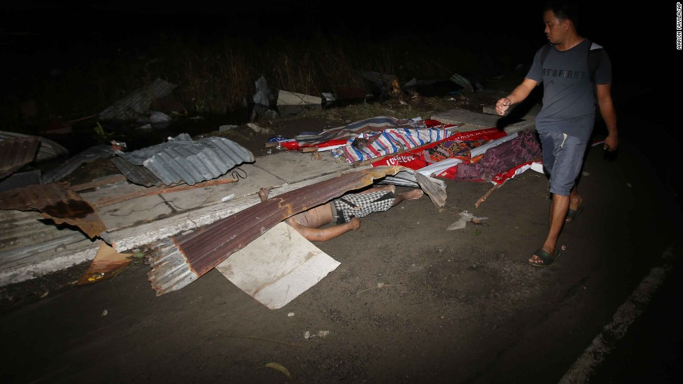A resident passes victims' bodies on a Tacloban street November 9.