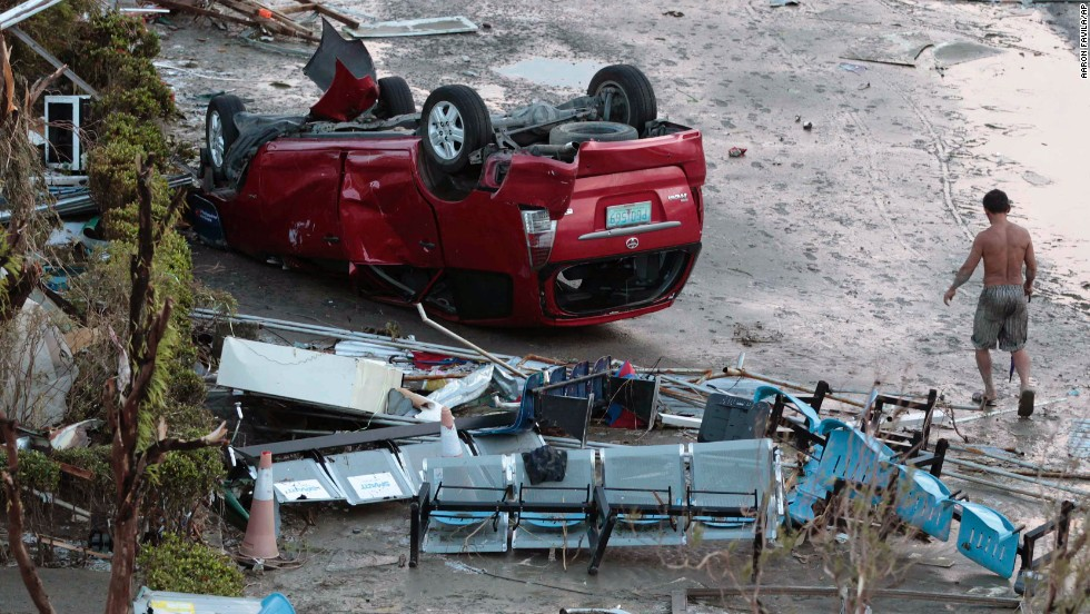 A resident passes an overturned car in Tacloban on November 9.