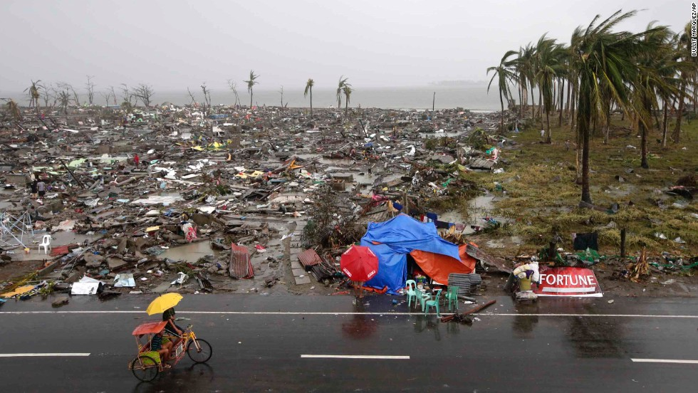 People ride past destruction in Tacloban on Sunday, November 10.