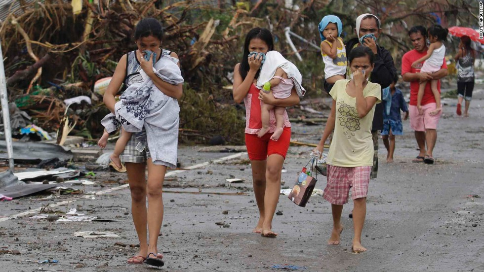 People cover their noses to block the smell of bodies in Tacloban on November 10.