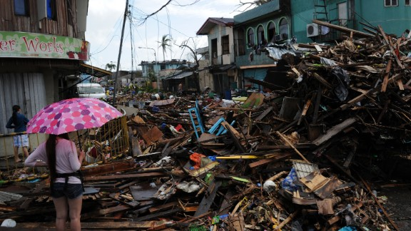 A resident stands amongst a pile of debris washed inland along a road in Tacloban, Leyte province, central Philippines on November 10, 2013, three days after devastating Typhoon Haiyan hit the city on November 8.