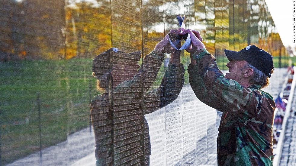 A man traces the name of a fallen soldier Monday from the wall of the Vietnam Veterans Memorial.