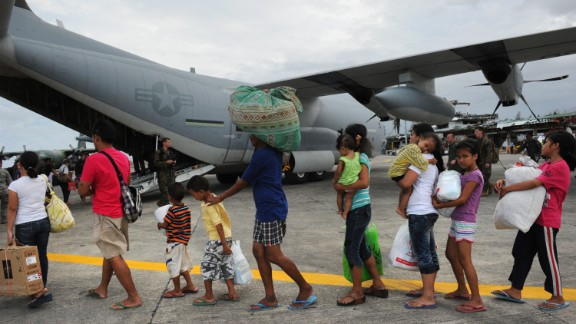 Typhoon survivors line up at the Tacloban airport on November 11 to board a U.S. military plane bound for Manila.