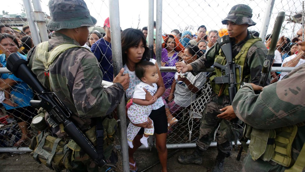 Soldiers let a woman and her child through a fence to get food November 11 outside the Tacloban airport.