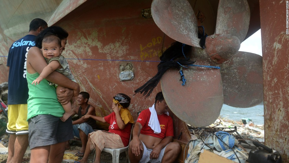 Residents of Anibong, Philippines, rest November 11 near a ship propeller that washed ashore during the storm.