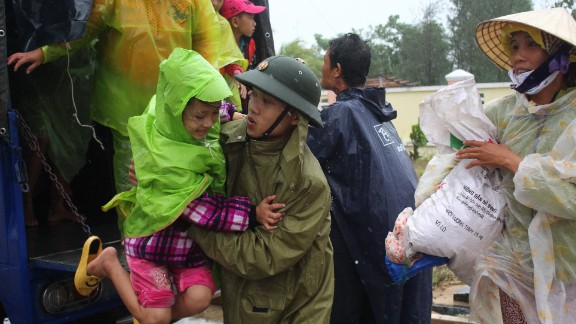 A Vietnamese soldier assists a girl Saturday, November 9, as villagers are moved in the central province of Quang Nam.